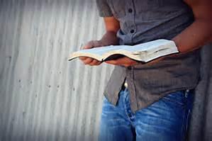 man standing reading Bible